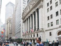 U.S. flags and tourists in front of NY Stock Exchange facing Bro. New York, NY, June 16 2015: New York Stock Exchange facing Broad Street; tourists stroll stock photography