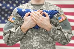 U S La tenuta del soldato dell'esercito ha piegato la bandiera di U.S.A. prima del suo petto fotografie stock libere da diritti