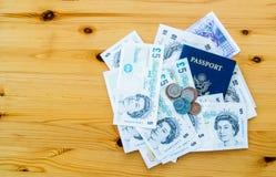 U S pass och brittpengar på en trätabell Royaltyfri Bild