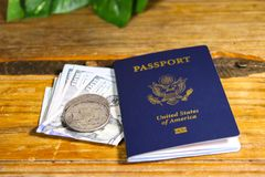 U.S. Passport with Cash and Silver depicting the cost of International travel. U.S. Passport on a vintage wood table with lot`s of money and even silver for Royalty Free Stock Photo