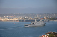 U.S.S New Orleans and U.S.S. Ronald Reagan Navy Ships. The U.S.S. New Orleans, San Antonio class amphibious transport dock coming into San Diego Bay, while the U royalty free stock photography