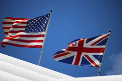 U.S. and UK flags in the blue sky Stock Photos