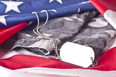 U.S. Veteran Memorial. An blank army veteran dogtag and camouflage uniform pants draped among a flag of the United States Royalty Free Stock Photos