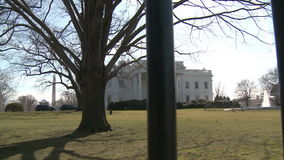 U.S. White House Behind the Fence. Looking across the North Lawn from Pennsylvania Avenue at the White House in Washington, D.C. The camera moves across the stock video footage