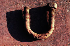 U-shape bolt. Old rusty u-shape screw bolt on corroded metal surface with shadow Royalty Free Stock Image