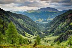U-shaped valley with forests and meadows Carnic Alps Austria. U-shaped valley with lush green forests and meadows in Karnische Alpen with Eggenkofel peak of Stock Image