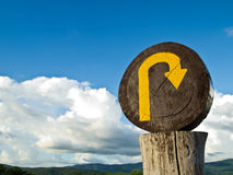 U turn sign. A wooden U turn sign on the top of the mountain with bright sky Royalty Free Stock Photography