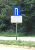 U turn signage. Road signage white symbol U turn with blue backgorund. Below blank white rust board Stock Photos