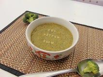 u. x22; Erhalten Sie besseres soon& x22; geschrieben in Gemüsesuppe mit Löffel Lizenzfreie Stockfotografie