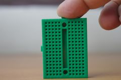 Użytkownik stuka zielonego protoboard pionowo Zdjęcie Royalty Free