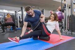??UA?28-03-2019 做与个人教练员的成熟妇女体育锻炼在健身房 协助老妇人的男性辅导员 图库摄影