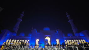 UAE, 2017: Believers and the women in front of the mosque Muslim. UAE, 2017: Mosque in Abu Dhabi, in the evening light. Fountain in front of the mosque. The stock video footage