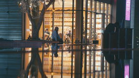 UAE, 2017: Bright storefront. Light at the shop in the evening hours. Urban residents and passers-by walk past a store with a yellow showcase stock footage