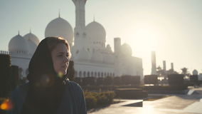 UAE, 2017: Caucasian woman in hijab on background Sheikh Zayed Mosque stock video footage