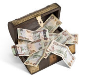 UAE Dirham bank notes in a trunk_1. An old wooden trunk filled with UAE Dirhams bank notes Royalty Free Stock Images