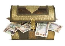 UAE Dirham bank notes in a trunk_2. An old wooden trunk filled with UAE Dirhams bank notes Royalty Free Stock Photography