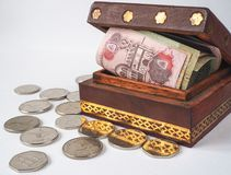 Arabic dirhams in the old wooden box. UAE dirham currency notes and coins royalty free stock images