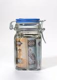Uae dirhams in jar. UAE currency in a glass jar royalty free stock images