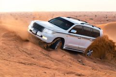UAE, Fujairah 2017.19.11 Off-road safari on jeeps SUVs in the Arab orange-red sands desert in the sunset sun stock image