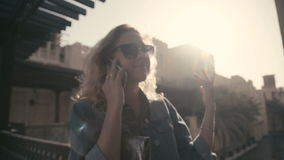 UAE, 2017: Madinat jumeirah. Woman in sunglasses talking on the phone. UAE, 2017: Beautiful young woman in sunglasses standing on the background of the sun and stock video