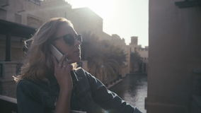 UAE, 2017: Madinat jumeirah. Young woman in sunglasses talking on the phone. UAE, 2017: Madinat jumeirah. Beautiful young woman in sunglasses standing on the stock video footage