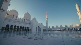 UAE, 2017: The minaret of the main prayer hall and a large white mosque. Of Sheikh Zayed in Abu Dhabi. Columns and dome of the mosque. Attraction UAE and stock footage