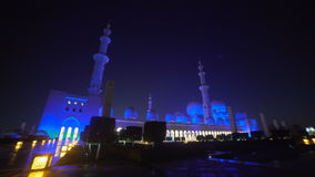 UAE, 2017: Mosque in Abu Dhabi, in the evening light. Fountain in front of the mosque. The mosque is illuminated in blue. Believers and the women in front of stock footage