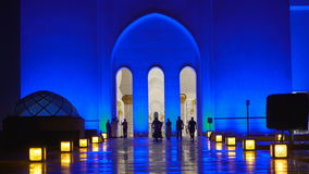 UAE, 2017: Mosque in Abu Dhabi, in the evening light. The road to the mosque, consecrated lanterns. The mosque is illuminated in blue. Believers in front of stock video