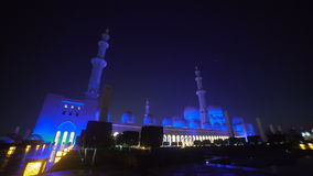 UAE, 2017: The mosque in Abu Dhabi is illuminated in blue. UAE, 2017: Sheikh zayed grand mosque. Mosque in Abu Dhabi, in the evening light. Fountain in front of stock video footage