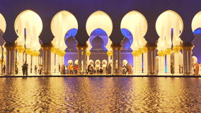 UAE, 2017: Mosque reflected in the water. Evening lights stock video