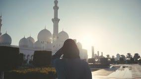 UAE, 2017: Mujer en hijab en el fondo Sheikh Zayed Mosque almacen de metraje de vídeo