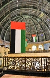 UAE national flags at the mall. Dubai. Garlands of lights, beautifully illuminated showcase, decorative railings Stock Image