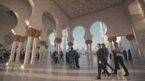 UAE, 2017: The sun`s rays shine through the pillars inside the mosque. UAE, 2017: Sheikh zayed grand mosque. Mosque in Abu Dhabi. A tourist and Muslims of stock video