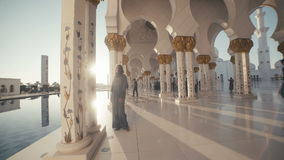 UAE, 2017: The sun`s rays shine through the pillars inside the mosque. UAE, 2017: Sheikh zayed grand mosque. A young woman in the traditional dress of Muslim stock footage
