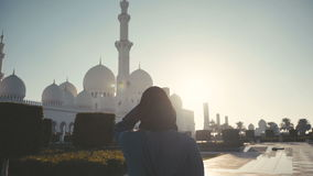 UAE, 2017: Woman in hijab on background Sheikh Zayed Mosque stock video footage