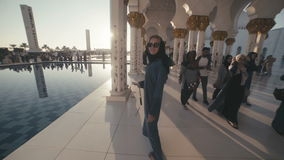 UAE, 2017: A woman in the traditional dress of Muslim inside the mosque. UAE, 2017: Sheikh zayed grand mosque. Mosque in Abu Dhabi. A young woman of European stock video