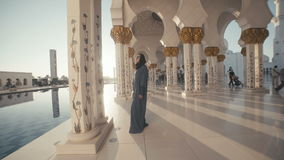 UAE, 2017: women in black Abai - walking inside the mosque. UAE, 2017: A young woman of European appearance in the traditional dress of Muslim women - black stock footage