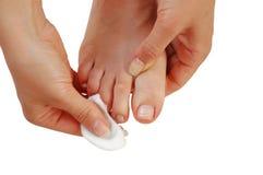 Uñas del dedo del pie de la limpieza de la mujer joven Imagen de archivo libre de regalías