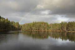 Uath Lochan and Rainbow in Glen Feshie in the Highlands of Scotland stock photography