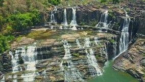 UAV Camera Hangs over Waterfalls Cascade among Rocks. UAV camera hangs over picturesque wide waterfalls cascade among rocks in tropical highland landscape stock footage