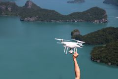 UAV or Drone camera fly up from the hands into the blue sky with. Ocean and island views on the mountain in Thailand Royalty Free Stock Image