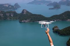 UAV or Drone camera fly up from the hands into the blue sky with. Ocean and island views on the mountain in Thailand Stock Image