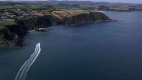 Speedboat chase in Cornwall. UAV Drone flying chasing a speed boat along the Cornish coastline near Mevagissey stock footage