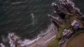 Drone camera looking down at Cornish rocks and coastline stock video footage