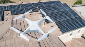 UAV Drone Inspecting Solar Panels On Large House. Roof Top stock image