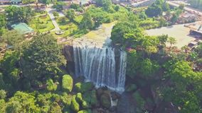 UAV Flies above and to Giant Waterfall by Tropical Park. UAV flies above and to fantastic famous waterfall running among green tropical park in vicinity of Dalat stock footage
