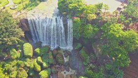 UAV flies close to waterfall bottom with large green boulders stock video footage