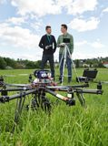 UAV Helicopter And Technicians At Park. UAV helicopter on grass with technicians in discussing background at park royalty free stock photos