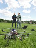 UAV Helicopter And Technicians At Park. View of UAV helicopter on grass with technicians discussing in background at park stock photos