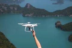 UAV of Hommel de camera vliegt omhoog van de handen in de blauwe hemel met Stock Fotografie